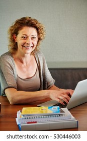 Close up portrait of smiling woman working from home on laptop