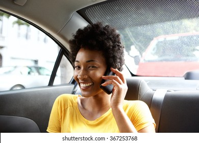 Close up portrait of smiling young african woman sitting in back seat of a car talking on mobile phone