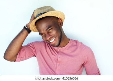 Close up portrait of smiling young african man with hat standing against white background