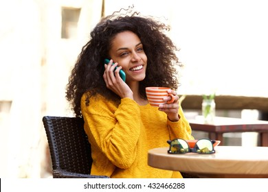 Close up portrait of smiling young african american woman talking on cellphone at outdoor cafe