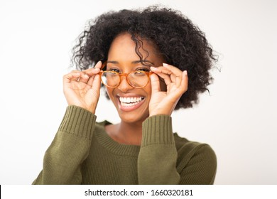 Close up portrait smiling young black woman with glasses against white isolated background