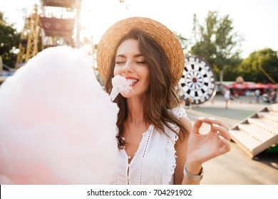 Close up portrait of a smiling young girl eating cotton candy at amusement park