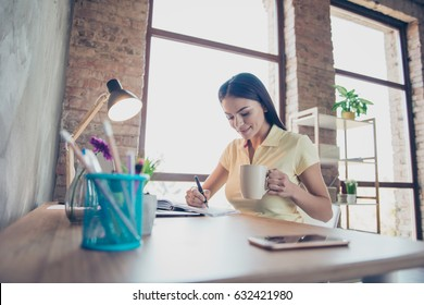 Close up portrait of a smiling young hispanic girl is drinking tea at the  office and making notes in nice light work station