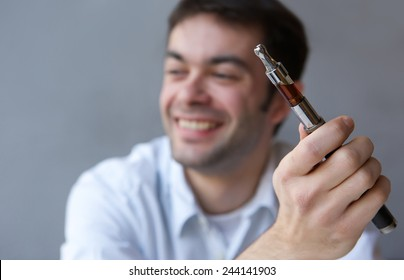 Close up portrait of a smiling young man with electric cigarette