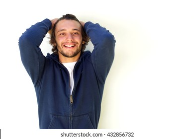 Close up portrait of smiling young man with hands in hair standing against white background