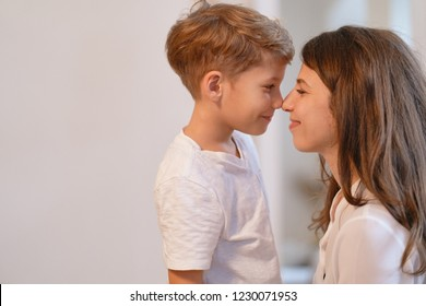 Close up portrait of smiling young mother and her preschool son touching noses.