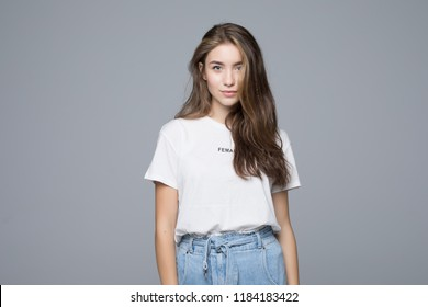Close up portrait of smiling young woman in white t-shirt looking at camera, isolated on gray background