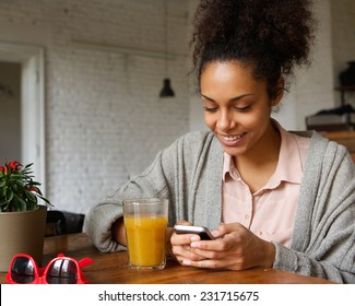 Close up portrait of a smiling young woman looking at mobile phone