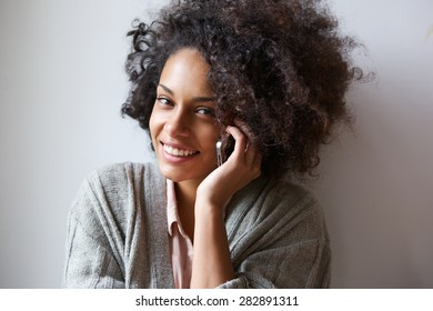 Close up portrait of a smiling young woman using mobile phone