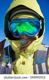 Close up portrait of snowboarder girl in bright clothes and green snowboarder mask on face, blue sky and sunny weather on background.
