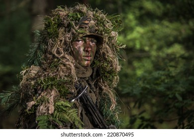 close portrait of the soldier wearing ghillie suit, face painted with camouflage paints