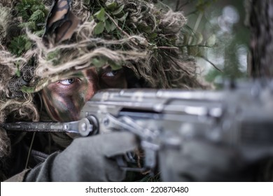 close portrait of special forces soldier dressed in ghillie suit, aiming with assault rifle