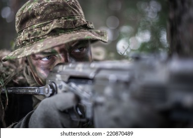 close portrait of special forces soldier wearing boonie hat, aiming with machine gun.