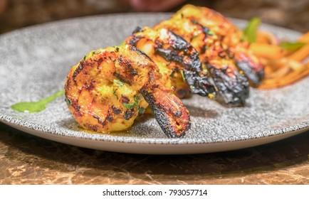 close up portrait of spicy indian tandoori prawn.