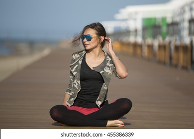 Close up portrait of an sport woman smiling and jogging outdoors by the beach.