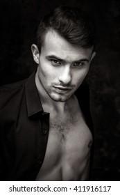 Close up portrait of Strong Athletic Man Fitness Model on dark background black and white photo