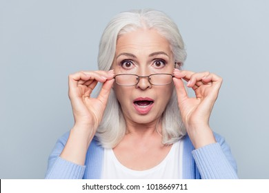 Close up portrait of stylish, aged, charming, surprised, shocked woman holding eyelets peek out glasses with wide open eyes and mouth over grey background