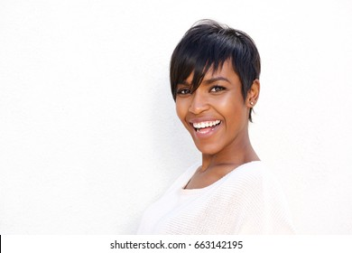 Close up portrait of stylish young black woman laughing against white background