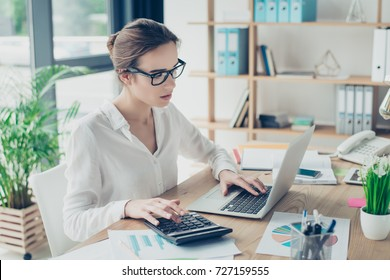 Close up portrait of successful business woman economist in formal wear, sitting at her work place in a light modern design office, making report, in front of laptop, stylish, ponder, pensive