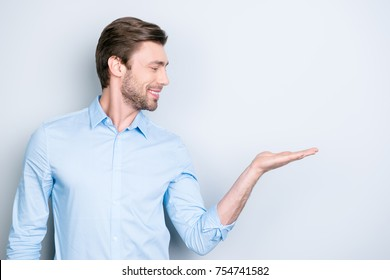Close up portrait of successful cheerful cute young man presenting new product, showing copy spase on her palm on grey background