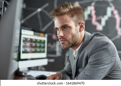 Close up portrait of successful trader looking focused while sitting in front of monitors in the office. Blackboard full of charts and data analyses in background. Stock trading, business concept