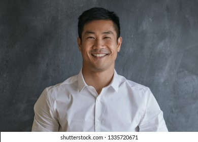 Close up portrait of a successfull young Asian businessman smiling confidently while standing in front of a blank chalkboard in an office