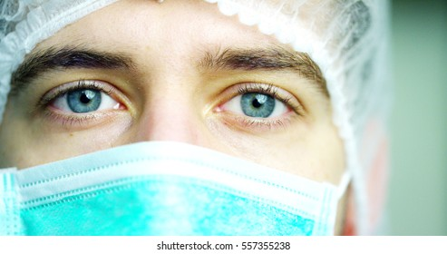 close up portrait of a surgeon or doctor with mask and headset ready for operation in hospital or clinic. The surgeon smiles safe and proud of himself. Concept of medicine, hospitals and doctors, care