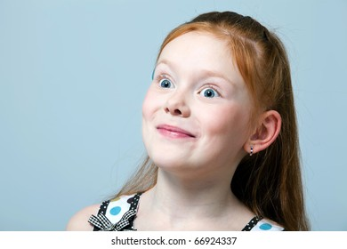 Close up portrait of a surprised red-haired girl indoors