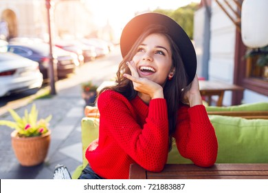 Close up portrait of surprised  tourist Woman in stylish black hat and autumn bright red sweater sitting in city cafe on street and enjoying amazing vacation time.
