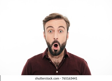 Close up portrait of a surprised young bearded man looking at camera with open mouth isolated over white background