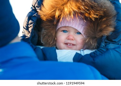 Close up portrait of sweet newborn girl wrapped in winter envelope outdoors