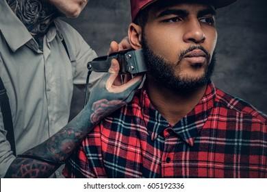 Close up portrait of tattooed male barber cuts, beard to a Black male.