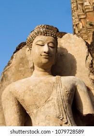 Close portrait of Tawaarawadee eras buddha in the sunlight at Wat Phra Si Rattana Mahathat, Chaliang. Si Satchanalai historical park, world heritage of Sukhothai province, Thailand.