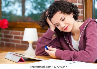 Close up portrait of teen girl at desk wondering over math problem.