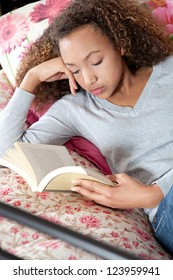 Close up portrait of a teenage girl reading a book while laying down on her bed at home, relaxing.