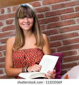 Close up portrait of teenage girl sitting with reading book.