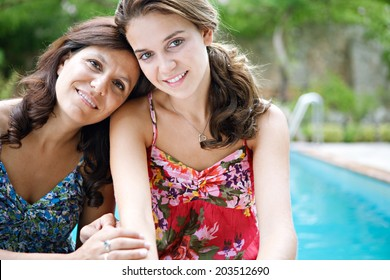 Close up portrait of a teenager daughter and her mother hugging and smiling during a summer holiday break in a vacation villa green garden and swimming pool, relaxing together. Outdoors lifestyle.