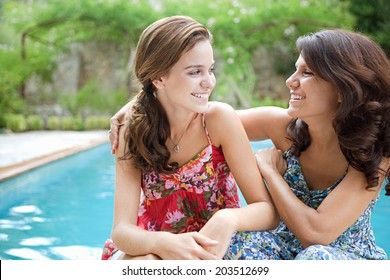 Close up portrait of a teenager daughter and her mother together, joyfully smiling during a summer holiday break in a vacation villa green garden and swimming pool, relaxing outdoors lifestyle.