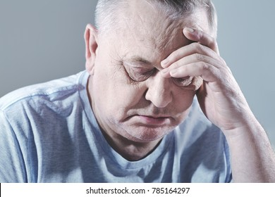 Close up portrait of thoughtful aged man in t-shirt sitting with hand on head - depression concept