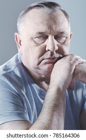 Close up portrait of thoughtful aged man in t-shirt sitting with hand under head - depression concept