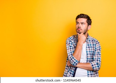Close up portrait of thoughtful man who looks away touching his chin and weighs the pluses and minuses of the offer isolated on bright yellow background with copy space for text