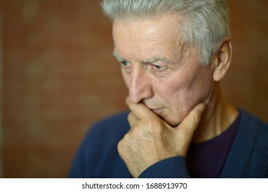 Close up portrait of thoughtful senior man at home