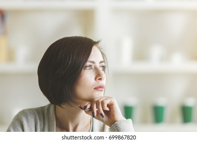 Close up portrait of thoughtful woman on blurry office background. Headshot concept