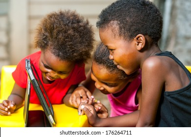 Close up portrait of three African young girls playing together on digital tablet.