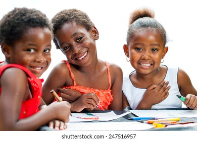 Close up portrait of three cute some African girlfriends drawing together.Isolated on white background.