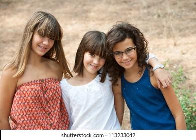 Close up portrait of three cute teenage girlfriends outdoors.