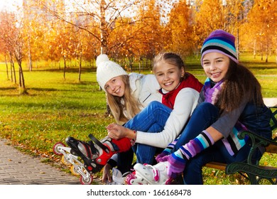 Close portrait of three happy girls putting on roller blades sitting in the park