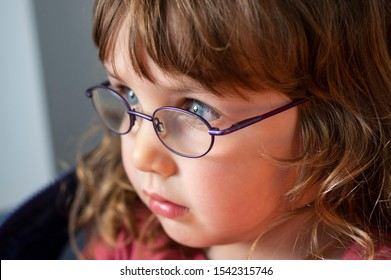 Close up portrait of a three years old blue eyed blond girl with eye glasses looking into the light.