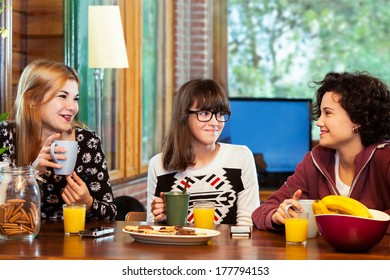 Close up portrait of three young girls having conversation over breakfast at home.