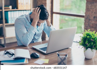 Close up portrait of tired sick young brunet man with strong migraine. He is wearing the formalwear, sitting at the workplace, holding his head, upset